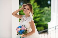 Portrait of a laughing bride in a lace dress and a bouquet of different colors. The girl is standing on the street and stock image