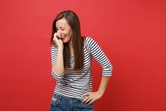 Portrait of laughing cheerful young woman in striped clothes keeping hand near face, covering isolated on bright red. Wall background. People sincere emotions royalty free stock photo