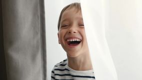Portrait of a laughing child. A cute boy looks into the camera and shows joy and happiness. Children`s emotions.