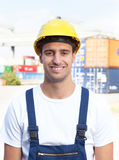 Portrait of a laughing docker. On a seaport with containers for oversea in the background Royalty Free Stock Image