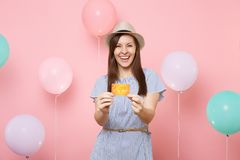 Portrait of laughing fascinating young woman in straw summer hat and blue dress holding credit card on pastel pink. Background with colorful air balloons royalty free stock photography