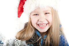 Portrait of a laughing girl with blue eyes in a Ch. Cute Portrait of a laughing girl with blue eyes in a Christmas hat with a Christmas tree Stock Images