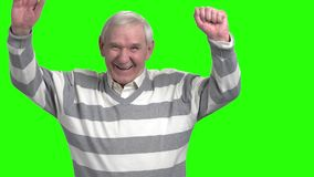 Portrait of laughing granddad, slow-motion. Happy laughing grandpa putting hands up against green hromakey background stock footage