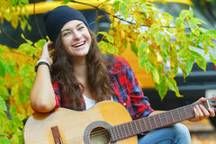 Portrait of laughing guitar player girl squatting at yellow van and autumn tree leaves background Royalty Free Stock Photo