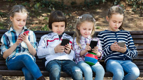 Portrait of laughing kids playing with phones Royalty Free Stock Photo