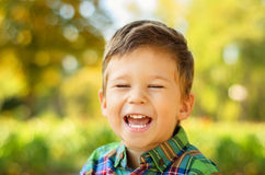Portrait of laughing little boy. Closeup portrait of a cute laughing little boy with eyes closed in summer park Stock Photo