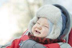 Portrait of a laughing little boy in a fur hat with a fur hat for a winter walk. Smile Royalty Free Stock Photography