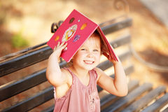 Portrait of laughing little girl with a book on his head Royalty Free Stock Photo