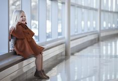 Portrait of laughing little girl wearing coat sitting in mall. Portrait of laughing little girl wearing orange coat sitting in shopping mall. Child fall fashion Stock Photo