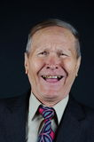 Portrait of laughing man. Businessman laughing looking at camera black background Stock Photos