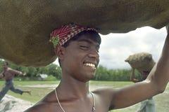 Portrait laughing man lugging burlap bag Bangladesh Royalty Free Stock Photography