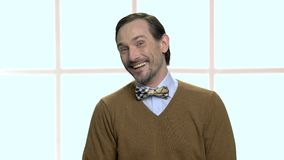 Portrait of laughing mature man with beard. Joyful caucasian man with brown sweater and bow tie. Checkered window background stock video