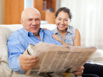 Portrait of laughing mature woman and elderly man with newspaper Royalty Free Stock Photo