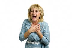 Portrait of laughing mature woman. Senior lady holding hands on chest and laughing with wide open mouth on white background Royalty Free Stock Image