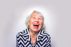 The portrait of a laughing old woman. The portrait of a laughing senior woman at studio Stock Images