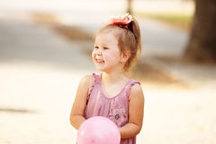 Portrait of laughing and playing a little girl holding a balloon Royalty Free Stock Photo