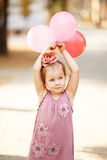 Portrait of laughing and playing little girl holding colorful ba Royalty Free Stock Image