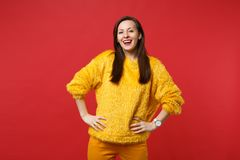 Portrait of laughing pretty young woman in yellow fur sweater standing with arms akimbo isolated on bright red wall. Background in studio. People sincere royalty free stock photo