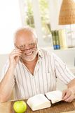 Portrait of laughing senior with book. Portrait of laughing senior looking at camera, sitting with book at table stock photos