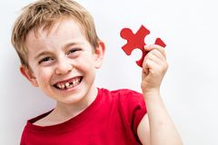 Laughing toothless boy finding jigsaw for concept of fun education royalty free stock images