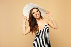 Portrait of laughing woman in black and white striped dress, hat standing, looking camera isolated on pastel beige