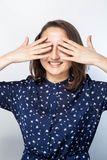 Portrait of a laughing woman closing her eyes with hands over white background. ,. Waiting for a surprise stock photo