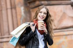portrait of laughing woman with shopping bags and coffee to go stock images