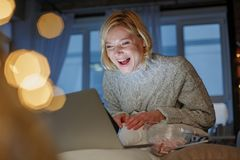 Joyful lady having fun during weekend. Portrait of laughing woman using laptop while relaxing on holiday. Her face expressing positive emotions Royalty Free Stock Photos