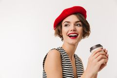 Portrait of a laughing woman wearing red beret. Holding cup of coffee and looking away isolated over white background Stock Image