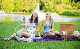 Portrait of the laughing women sitting on the purple blanket Royalty Free Stock Photo