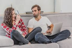 Portrait of a laughing young couple shopping online while sitting on a couch with credit card and laptop computer. royalty free stock photo