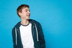 Portrait of laughing young man in casual clothes standing, looking aside isolated on blue wall background in studio royalty free stock photo