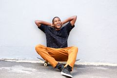 Laughing young man sitting on skateboard against a wall Stock Image