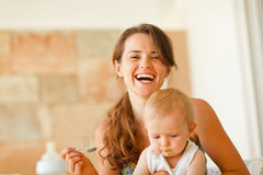 Portrait of laughing young mother feeding baby Royalty Free Stock Photos