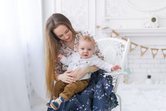 Portrait of laughing young mum together with a small son in a white room interior Royalty Free Stock Photo