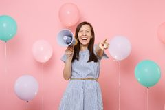 Portrait of laughing young pretty woman in blue dress holding megaphone pointing index finger on camera on pink