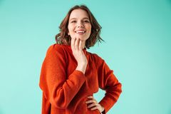 Portrait of a laughing young woman dressed in sweater. Looking at camera  over blue background Stock Images