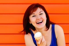 Portrait of a laughing young woman holding an ice cream in waffle cone. Orange wall in background. Happy lifestyle concept. Place stock photography