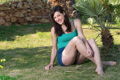 Portrait of laughing young woman relaxing on grass with palm tr Royalty Free Stock Image