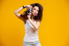 Portrait of laughing young woman taking pictures on retro vintage photo camera isolated on bright yellow background. People sincere emotions, lifestyle concept stock image
