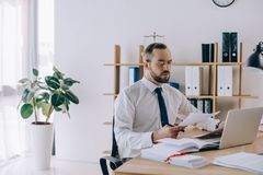 Portrait of lawyer with documents sitting at workplace with laptop. In office stock photography