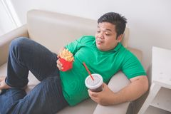 Lazy obese person eats junk food while laying on a couch. Portrait of lazy obese person eats junk food while laying on a couch Stock Images