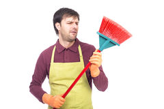 Portrait of lazy young man holding a sweep,conceptual image, Royalty Free Stock Images