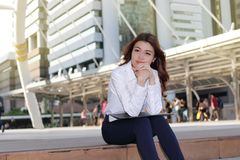 Portrait of leader young Asian business woman thinking and sitting on stairway in urban building background. Portrait of leader young Asian business woman Stock Photo