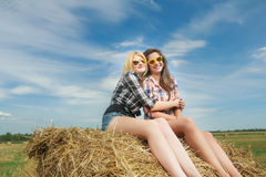 Portrait of leggy blonde and brunette girls posing on bundle of straw Royalty Free Stock Photography