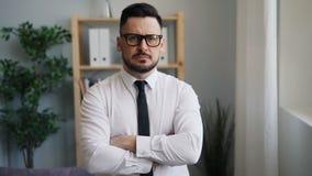 Portrait lent de moton d'homme d'affaires sérieux avec les bras croisés dans le bureau banque de vidéos