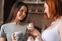 Portrait of lesbians looking to each. Just try it. Positive delighted women smiling and holding dessert in right hand while giving one cake to her friend Royalty Free Stock Images