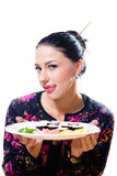Portrait of licking lips beautiful young woman having fun sitting at the table and holding sushi plate royalty free stock images