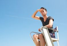 Portrait of a lifeguard sitting in chair on summer day stock photos