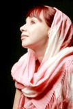 Portrait of likable woman. Beautiful woman in a pink shawl on a black background Royalty Free Stock Images